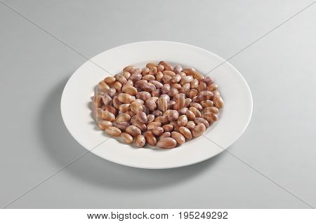 Round dish with a portion of boiled borlotti beans isolated on grey background