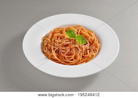 Round dish with a serving of spaghetti with tomato souce isolated on grey background