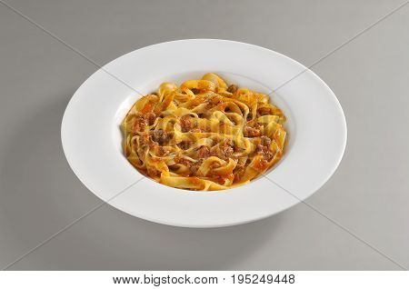 Round dish with a serving of tagliatelle pasta with meat souce isolated on grey background