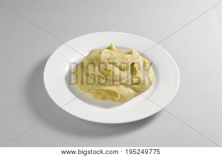 Round dish with puree of broad Beans and checkpeas isolated on grey background