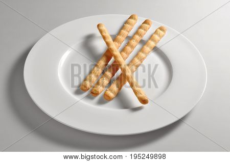 Round dish with salted breadsticks isolated on grey background