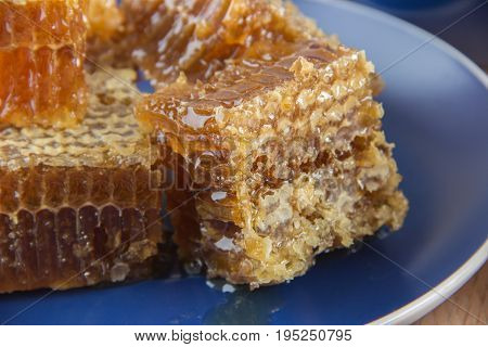 Golden honey in the comb in a jar and yellow lemon