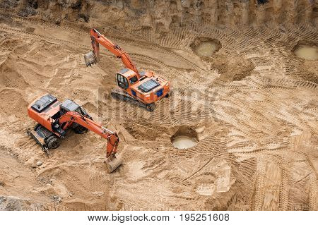 Excavators at sandpit during earthmoving works. Construction of concrete foundation of new building