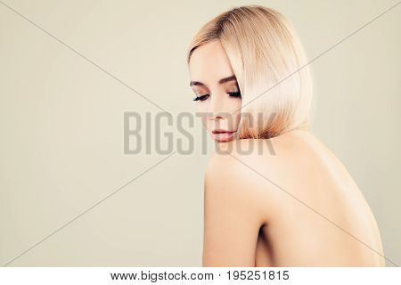 Sexy Blonde Woman Relaxing. Fashion Model on Background with Copy Space Female Back