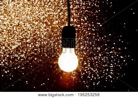 one light bulb on a black background  with sparkles