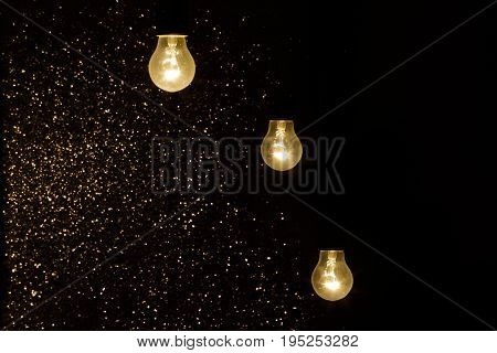 lot of light bulbs on a black background with sparkles