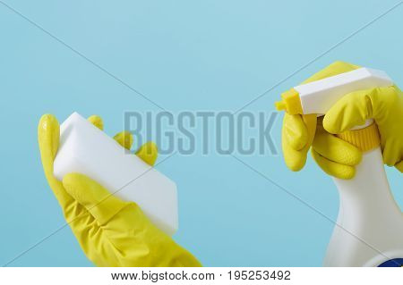 Hand in a rubber yellow glove holds spray bottle of liquid detergent and sponge on a blue background. cleaning