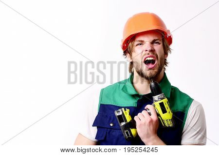 Finished work and simple building concept. Man with arrogant or angry face isolated on white background copy space. Builder in orange helmet and uniform. Repair worker holds yellow drill under chin