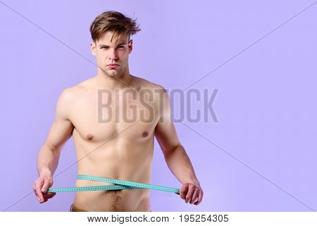 Young Sportsman With Cyan Measuring Tape On Light Purple Background