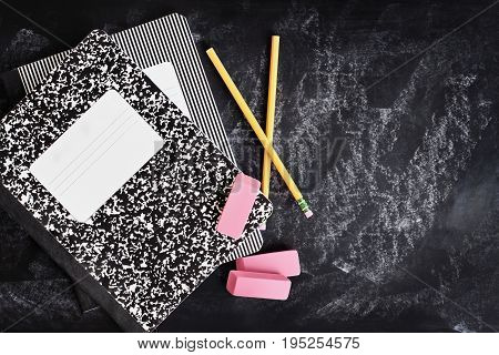 Back to school supplies. Books erasers and pencils over a chalkboard or blackboard with room for copy space.
