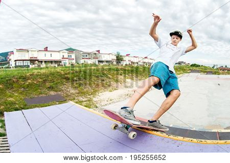 Teenager skater in a cap and shorts on rails on a skateboard in a skate park Wide angle
