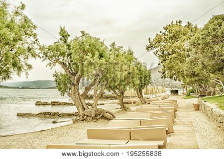 Deserted landscape with a deserted sea beach with sun beds and juniper trees on the Gulf of Mirabello Greece Crete. Photo tinted and styled