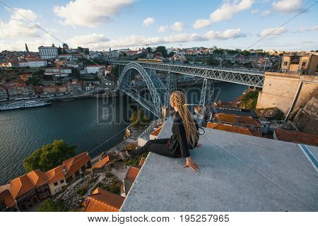 Woman with blond dreadlocks on the viewing platform opposite the Dom Luis I bridge across the Douro river in Porto, Portugal.