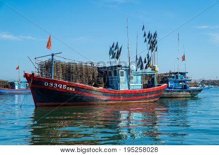 Hoi An, Vietnam - August 15, 2015: Vietnamese fishing boats on the Vin Cura Dai river, the mouth of the Thu Bon river near Hoi An in Vietnam.