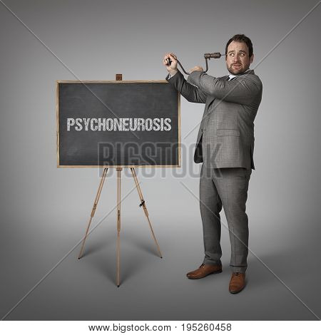 Psychoneurosis text on blackboard with businessman drilling his head