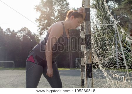 Exhausted overweight woman after a long workout in park