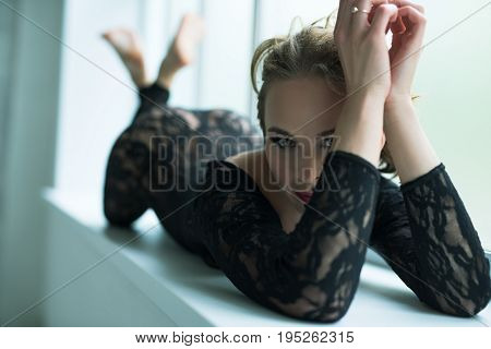 Passionate curly blonde with exquisite make up wearing seductive black lace underwear posing on window sill lying on her stomach studio shot