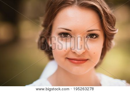 portrait of a young bride on the background of the park.