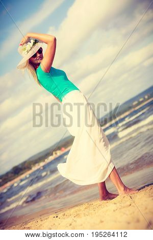 Summer time relax leisure concept. Attractive woman on the beach. Lady wearing sunglasses and hat