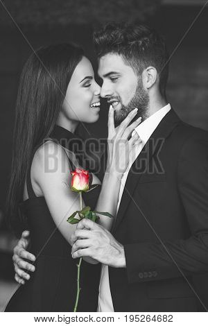 Happy young playful couple black and white with red rose love selective coloring
