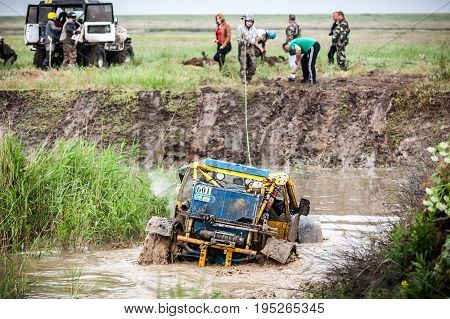 KIRILLOVKA UKRAINE - MAY 25 2016: Zaporizhia Trophy 2016. II stage of offroad trophy Ukrainian championship. Participants using winch to pass the swamp.