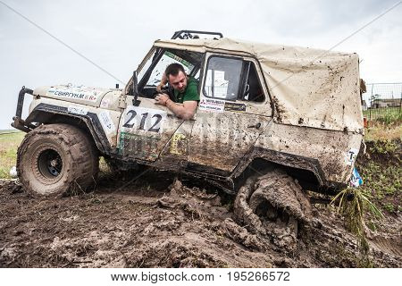 KIRILLOVKA UKRAINE - MAY 25 2016: Zaporizhia Trophy 2016. II stage of offroad trophy Ukrainian championship. Participant looking at flat tire.