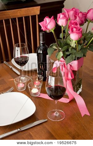 romantic dinner setting for two with wine and roses