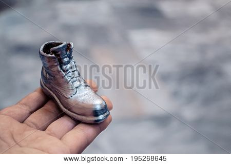 Object in the form of a boot printed on a 3d printer and covered with enamel on hand close-up. Isolated on white background. Progressive modern additive technology. Copy spase