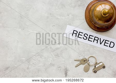 booking hotel room, ring and keys on gray stone desk background top view mock up