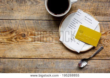 cup of coffee and receipt bill for payment by credit card on wooden table background top view mockup