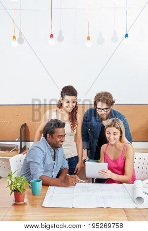 Young startup team meeting with tablet computer planning