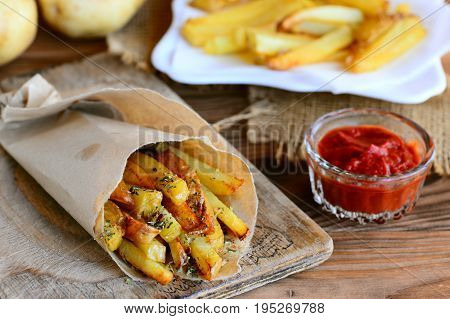 Crispy potato fries. Roasted sweet potato fries in paper and wooden board. Tomato sauce, raw potatoes on a wooden table. Rustic style