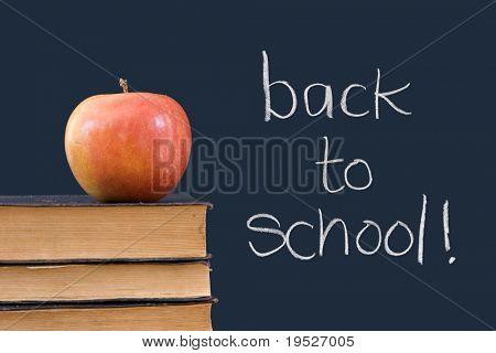 back to school written on chalkboard with apple, books