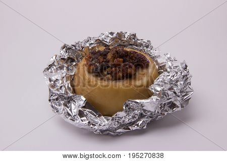 Yellow apple with walnuts raisins honey and cinnamon baked in foil on a white background