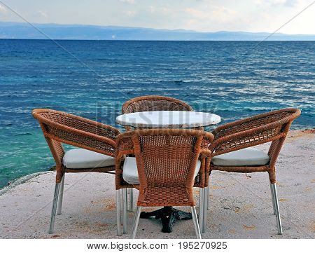 Wooden cafe chairs and table in front of Mediterranean sea
