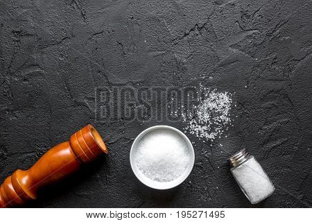 salt in bottle and saltcellar on black stone kitchen table background top view mock-up