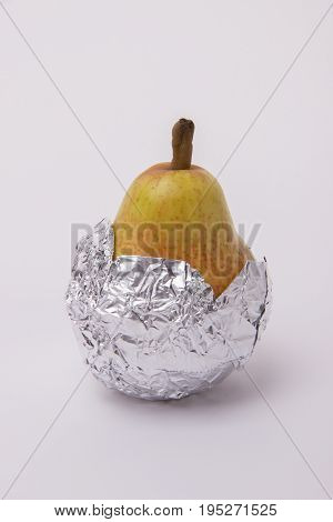 Yellow juicy pear wrapped in foil on a white background
