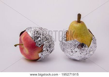 Yellow juicy pear and red apple wrapped in foil on a white background