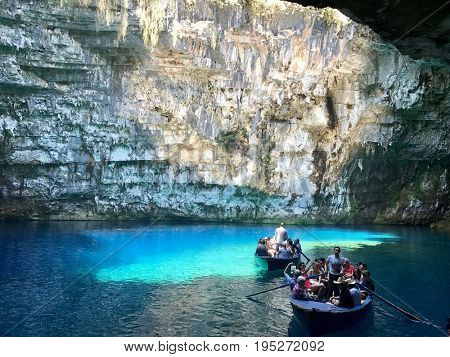 KEFALONIA - JULY 8, 2017: Tourists on boats on the Melissani Cave Lake in Sami, Kefalonia, Greece.