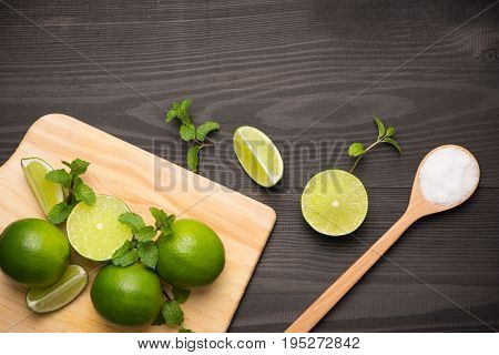 Fresh limes on cutting board on wooden table with spoon of salt. Top view background.