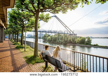 DUSSELDORF, GERMANY - July 04, 2017: View on the Rhinenpark with couple sitting on the bench enjoying great view on bridge and Rhine river in Dusseldorf