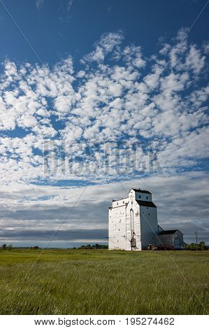 Vertical Crop of Wooden Grain Elevator Under Gorgeous Blue Sky