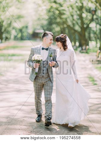 The walk of the smiling newlyweds in the sunny park