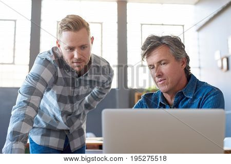 Two casually dressed businessmen looking focused and talking together over a laptop while working at a table in a modern office
