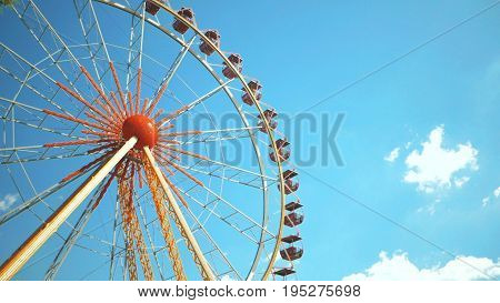 Underside view of a ferris wheel over blue sky. Ferris wheel at amusement park