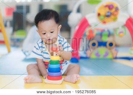 Adorable Asian baby boy 9 months sitting and playing with color developmental toys in kids room at home.