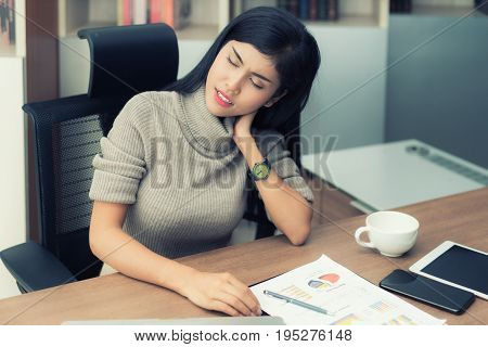 Asian young businesswoman having pain in her neck. Neck pain at office during working hard.