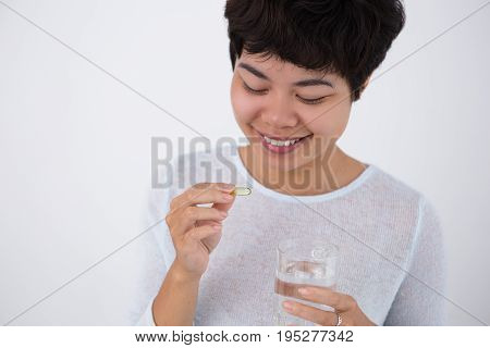 Closeup portrait of smiling young Asian woman holding glass of water and taking pill. Isolated front view on white background.