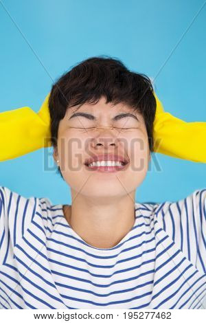 Closeup portrait of stressed young pretty Asian woman wearing protective gloves and clutching head with her eyes closed. Isolated view on blue background.