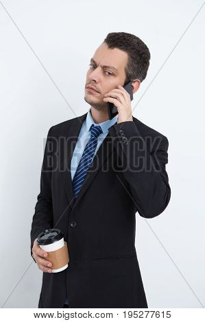 Serious busy male manager drinking coffee and talking on phone. Mobile young businessman working everywhere. He concentrated on conversation. Communication concept
